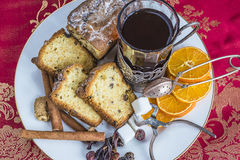Cake and tea. Christmas composition with sliced cake with raisins on a white dish, glass of tea in vintage glassholder, mandarins top view Stock Image