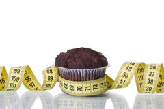 Cake temptation. A measure tape and a cake, bad food temptation concept (selective and soft focus stock image