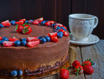 Cake Three chocolate with fresh berries and cup of tea Stock Photos