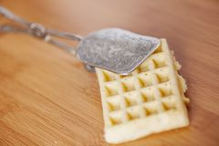Cake tongs with cake near. Cake tongs gripp a waffle on wooden table underground Background royalty free stock photos