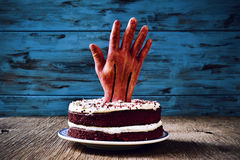 Cake topped with a bloody hand for halloween Royalty Free Stock Photos
