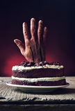 Cake topped with a bloody hand in a scary scene for halloween Royalty Free Stock Photography