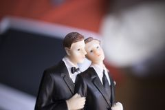 Cake topper gay wedding couple. Of two male grooms holding romantic marriage embrace of LGBT love Royalty Free Stock Photo