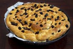 Cake van brood met droge rozijnen in een ronde bakselpan die wordt gemaakt stock foto