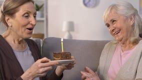 Cake van de bejaarde wenst de gifting verjaardag aan vriend, dame het maken en slagenkaars dit stock video