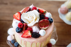 Cake with various berries, figs, meringues and rose on top. Stock Photo