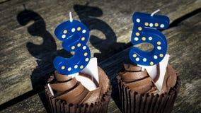 Cake Vijfendertig van de het Suikerglazuurkop van de Chocoladesmaak Blauwe Geel Stock Afbeelding