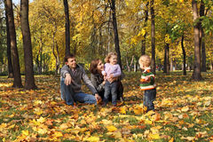 A cake walk. A family with two children walking in the autumn park among the fallen leaves Royalty Free Stock Photography
