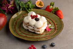 Cake with whipped cream and berries on a green plate royalty free stock photography