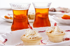 Cake with whipped cream and tea in glass glasses. High key. Soft light Stock Photography