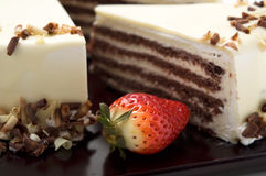 Cake with white chocolate. And strawberry on the wooden plate stock photos