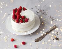 Cake with white cream and strawberries. Christmas lights stock photography