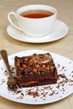 Chocolate cake and a cup of tea. Cake on a white plate with chocolate chips and tea Royalty Free Stock Photo