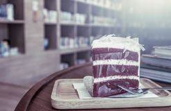 Cake on wooden table on blur bookshelf background Royalty Free Stock Photography
