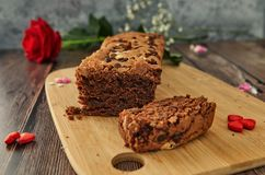 A cake on a wooden table with hearts and a rose royalty free stock photography