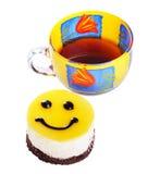 Cakeglimlach en een kop thee Royalty-vrije Stock Foto's