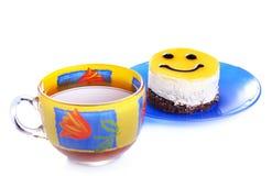 Cakeglimlach en een kop thee Stock Afbeelding