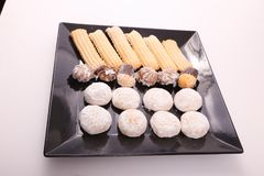 Petits fours, cakes and biscuits. Cakes, biscuits and petits fours presented in a black dish Stock Image