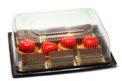 Cakes in box. Cakes in the transparent plastic box over white background Royalty Free Stock Images