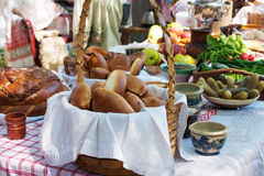 Cakes, bread, cucumbers, radishes and apples on a table outside Stock Photos