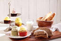 Cakes and breads. Cakes and whole wheat bread, baguette and milk are on the table Royalty Free Stock Photography