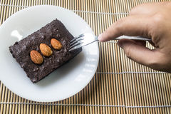 Cakes, brownies, sprinkle almonds are tasting. Stock Photography