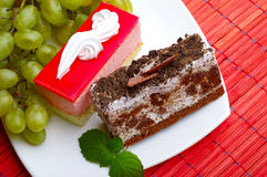 Cakes, a bunch of grapes and mint leaves Stock Photography