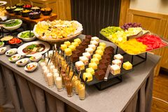 Cakes and cakes on a tray with fruit cut slices on a table. Cakes and cakes on a tray with fruit cut slices for a buffet table royalty free stock image