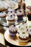 Cakes, candy bar at the wedding. Muffins on a golden plate stock image