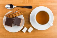 Cakes with chocolate in plate, cinnamon, sugar, tea and teaspoon Stock Images