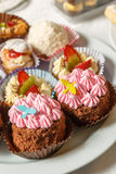 Cakes with cream, grated chocolate, sugar powder. Baking sweets for dessert in the shop window Stock Images