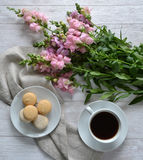 Cakes, a cup of coffee and flowers on the table. Royalty Free Stock Photo