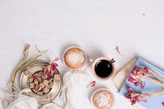 Cakes, cup of coffee and pink tulip flowers, romantic breakfast background. Copy space, top view. Royalty Free Stock Photography