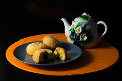 Cakes and cup of tea on the black background. Orange background Stock Photography