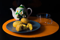 Cakes and cup of tea on the black background. Orange background Royalty Free Stock Photography