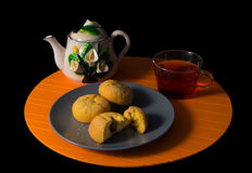 Cakes and cup of tea on the black background. Cakes and cup of tea on the black and orange background Stock Images