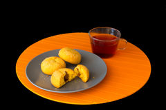 Cakes and cup of tea on the black background. Orange background Royalty Free Stock Photos