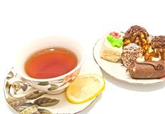 Cakes and cup of tea on white Royalty Free Stock Photo
