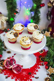 Cakes, cupcakes with dried lemon and chocolate on a white pedestal on a background of green Christmas garland and lights royalty free stock image