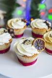 Cakes, cupcakes met droge citroen en chocolade op een wit voetstuk op een achtergrond van groene Kerstmisslinger en lichten Royalty-vrije Stock Fotografie