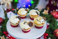 Cakes, cupcakes met droge citroen en chocolade op een wit voetstuk op een achtergrond van groene Kerstmisslinger en lichten Stock Foto's