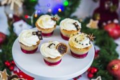 Cakes, cupcakes met droge citroen en chocolade op een wit voetstuk op een achtergrond van groene Kerstmisslinger en lichten Stock Afbeeldingen