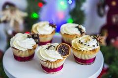 Cakes, cupcakes met droge citroen en chocolade op een wit voetstuk op een achtergrond van groene Kerstmisslinger en lichten Royalty-vrije Stock Afbeeldingen