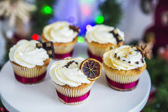 Cakes, cupcakes met droge citroen en chocolade op een wit voetstuk op een achtergrond van groene Kerstmisslinger en lichten Stock Fotografie