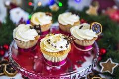 Cakes, cupcakes met droge citroen en chocolade op glastribune op een achtergrond van groene Kerstmisslinger en lichten Royalty-vrije Stock Fotografie