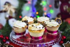 Cakes, cupcakes met droge citroen en chocolade op glastribune op een achtergrond van groene Kerstmisslinger en lichten Stock Foto's