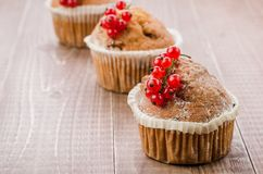 Cakes decorated with red berries on a wooden table/cakes decorated with red berries on a wooden table. copy space. Dessert cupcake berry currant sweet three royalty free stock photography