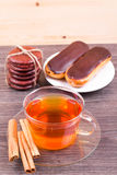 Cakes eclairs, and a cup of tea with cinnamon Royalty Free Stock Photography