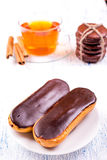 Cakes eclairs, and a cup of tea with cinnamon Royalty Free Stock Image