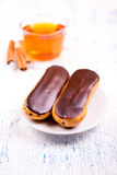 Cakes eclairs, and a cup of tea with cinnamon Royalty Free Stock Images